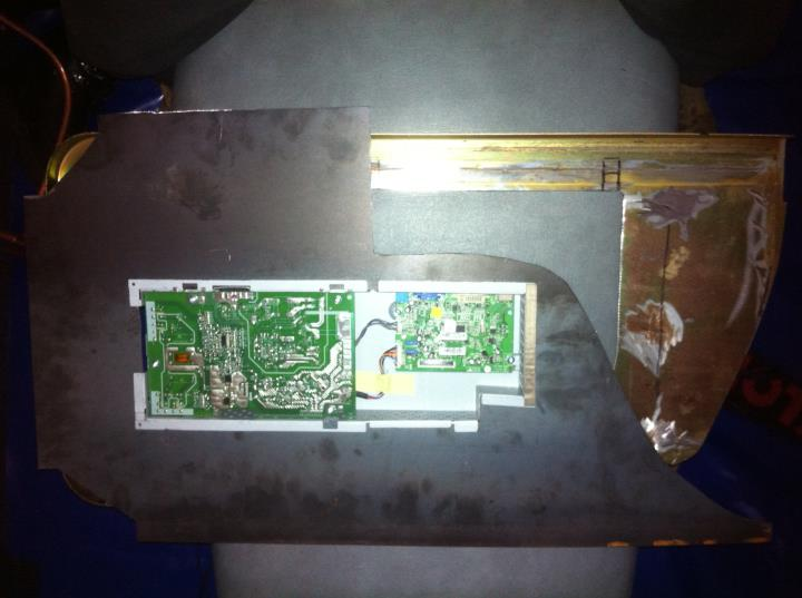 The circuitry box of the monitor fitted within the backpiece. prior to having bent the edges to fit within the surface housing piece.